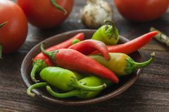 Ripe tomatoes, hot chili peppers, garlic on a wooden table Royalty Free Stock Images
