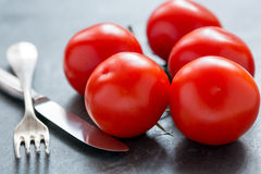 Ripe tomatoes, knife and fork. Royalty Free Stock Images