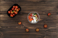 Ripe tomatoes lying round the bowl. Add some color. Big black bowl with tomatoes standing on the wooden table, fresh homemade salad being in plastic box in the royalty free stock photo