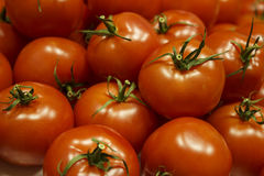 Ripe tomatoes. Many ripe tomatoes with green peduncles are heaped Stock Image