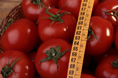 Ripe tomatoes and measuring tape Royalty Free Stock Images
