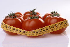 Ripe tomatoes and measuring tape Stock Image