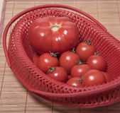 Ripe tomatoes in a red basket Stock Photos