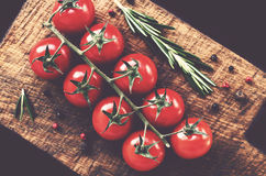 Ripe tomatoes, rosemary and spices on farmhouse wooden cutting board Stock Photo