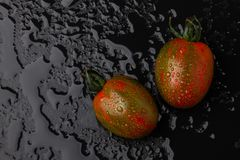 Ripe tomatoes on a wet black background. Top view Royalty Free Stock Image