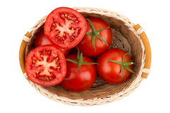 Ripe tomatoes in a wicker basket isolated on white background Stock Image
