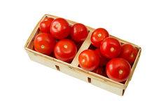 Ripe tomatoes in a wicker basket isolated on white. Stock Photo