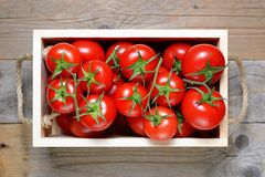 Ripe tomatoes in wooden box Stock Photo