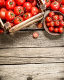 Ripe tomatoes in a wooden box. On a wooden table royalty free stock image