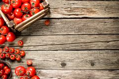 Ripe tomatoes in a wooden box. On a wooden table stock photography