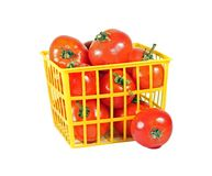 Ripe tomatoes in yellow basket isolated on white Royalty Free Stock Image