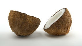 Ripe tropical coconut split in two halves rotating on a white background. Exotic fruits, loopabe. Ripe tropical coconut split in two halves rotating on a white stock video footage