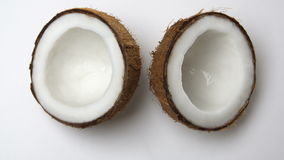 Ripe tropical coconut split in two halves rotating on a white background. Tropical fruits, loopable. Ripe tropical coconut split in two halves rotating on a stock video