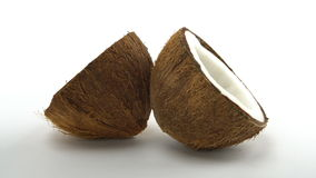 Ripe tropical coconut split in two halves rotating on a white background. Tropical fruits, loopable. Ripe tropical coconut split in two halves rotating on a stock footage