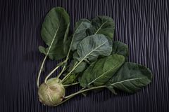 Ripe turnip with leaves on a wooden black background. Close up Stock Photos