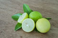 Ripe And Unripe Key Limes. On board surface, are yellow ripe, and green unripe key limes on leaves. One of the limes is cut in halves showing its inner pulp stock illustration