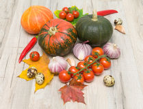 Ripe vegetables and autumn maple leaves on a wooden board Stock Photos