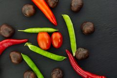 Ripe vegetables green pea fresh pod red chili pepper tomato cherry mix on a black background design base royalty free stock images