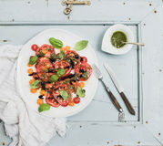 Ripe village heirloom tomato salad with olive oil and basil over light blue wooden background Stock Image