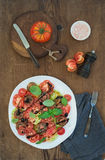 Ripe village heirloom tomato salad with olive oil, basil and spices over rustic wooden background Stock Photo