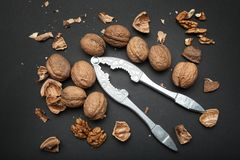 Ripe walnuts cracked with the help of an old nut cracker, a top view, a black background. Healthy food royalty free stock images
