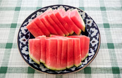 Ripe watermelon with apricots on oriental plate Stock Images