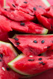 А ripe watermelon with black seeds sliced. Close-up. Royalty Free Stock Images