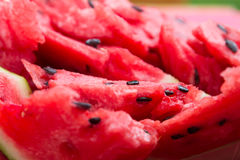 А ripe watermelon with black seeds sliced. Close-up. Stock Images