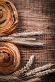 Ripe wheat ears fresh-baked rolls with raisins on oaken wooden b. Oard food and drink concept Stock Image