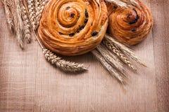 Ripe wheat ears raisin baked rolls on oaken wooden Stock Photo