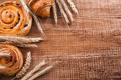 Ripe wheat ears raisin buns croissant on oaken. Wooden board food and drink concept Royalty Free Stock Photography