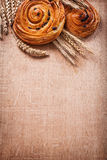 Ripe wheat ears rich raisin baked rolls on oaken. Wooden board food and drink concept Royalty Free Stock Photo