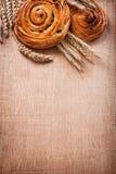 Ripe wheat ears rich raisin baked rolls on oaken Royalty Free Stock Photo