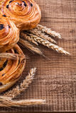Ripe wheat ears rich rolls with raisins on oaken Stock Photo