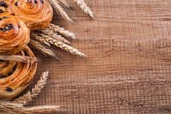 Ripe wheat ears sweet raisin buns on oaken wooden Royalty Free Stock Photo
