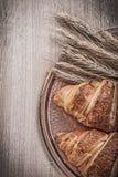 Ripe wheat rye ears sweet croissants brass tray on wooden board royalty free stock image