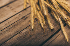 Ripe wheat spikelets on rural wooden table Stock Image