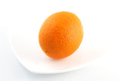Ripe whole orange on plate Royalty Free Stock Image