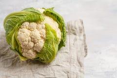 Ripe whole raw cauliflower on a light background on a napkin. He. Ripe whole raw cauliflower on a light background on a napkin Royalty Free Stock Image