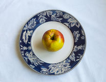 Ripe yellow Apple on a plate, white background Royalty Free Stock Image