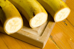 Ripe yellow bananas. Three ripe yellow cut bananas on a wooden cutting board Stock Photography
