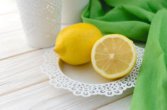Ripe yellow lemon in a beautiful white plate Royalty Free Stock Photography