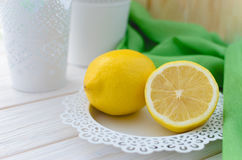 Ripe yellow lemon in a beautiful white plate Royalty Free Stock Photos
