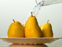 Ripe yellow pears and pouring water Royalty Free Stock Image