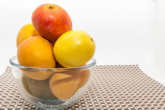 Ripe yellow and red mango fruits in glass bowl. On brown check mat Royalty Free Stock Photography