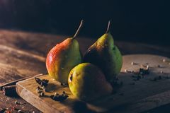 Ripe yellow with red tasty pears on the wooden board on the rustic dark brown wooden table and black background Stock Photos