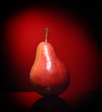 Ripen pear isolated on red background Royalty Free Stock Photos