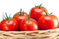The ripened tomatoes in a wattled basket on a white background Royalty Free Stock Photos