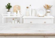 Ripiano del tavolo candeggiato con copyspace sopra la mobilia vaga della cucina con gli strumenti fotografia stock
