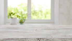 Ripiano del tavolo di legno d'annata candeggiato con la finestra vaga per l'esposizione del prodotto fotografia stock